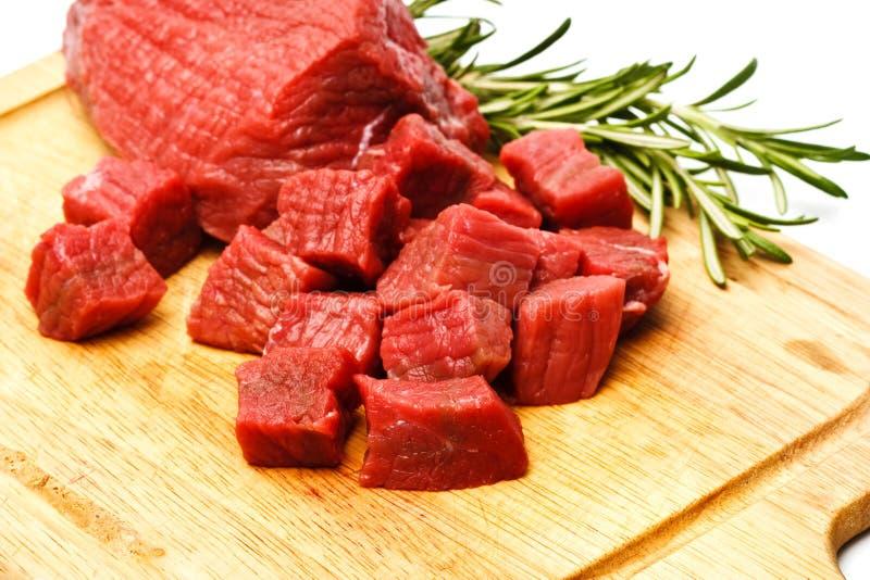 Cubos crudos de la carne fresca con verdes imagenes de archivo