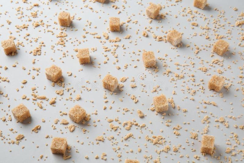 Cubos de Brown con las escamas del azúcar de arce en fondo gris fotografía de archivo libre de regalías