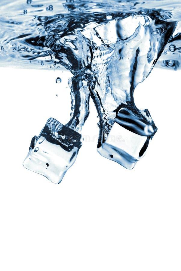 Cubos de gelo deixados cair na água com respingo imagens de stock