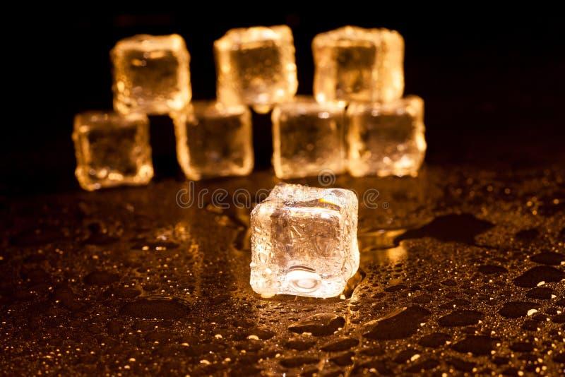 Cubos de gelo dourados no fundo preto fotos de stock royalty free