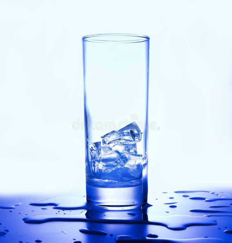 Cubos de gelo em um vidro Gotas de espalhamento Tom azul branco Vista lateral foto de stock royalty free
