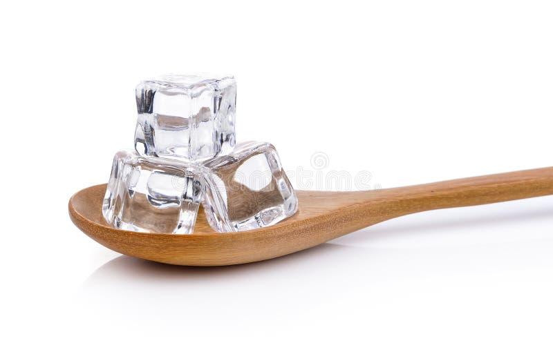Cubos de gelo na colher de madeira imagem de stock