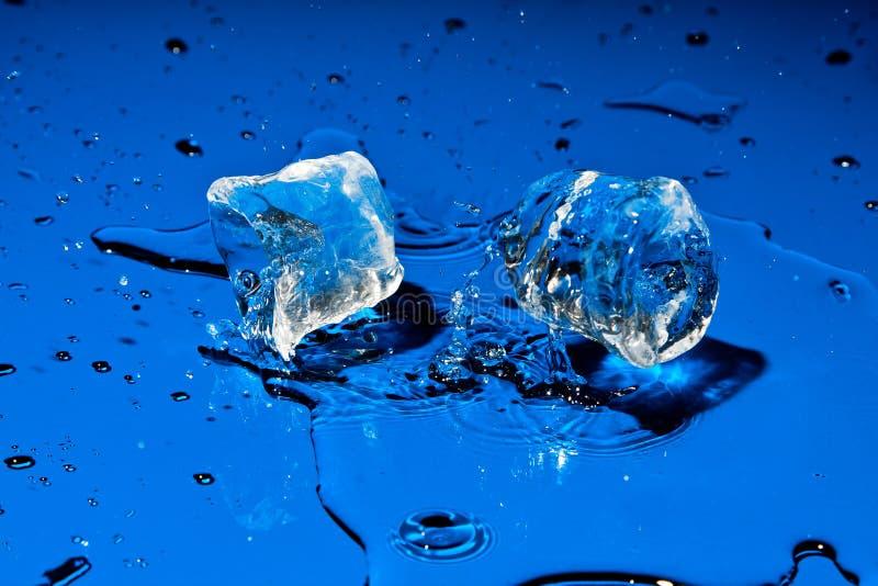 Cubos de gelo que caem na superfície azul imagens de stock royalty free