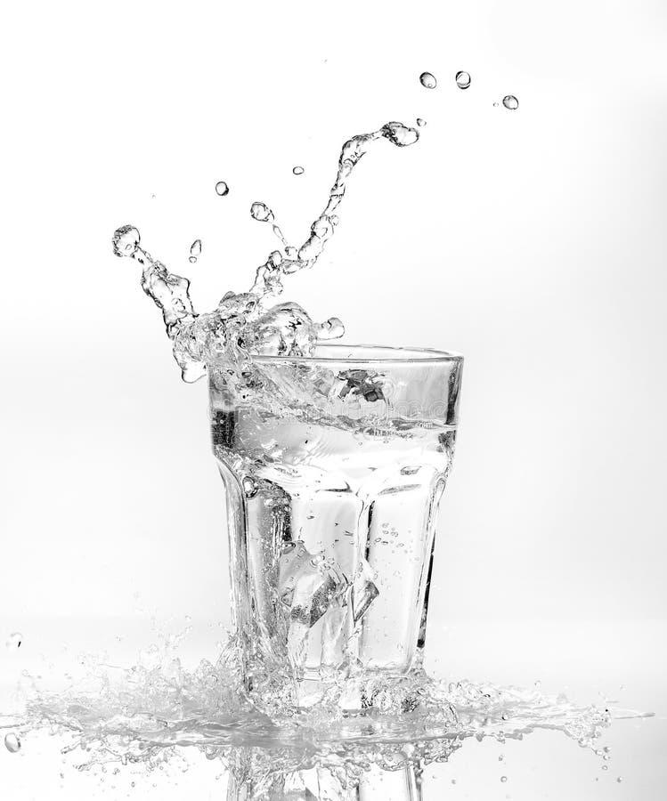 Cubos de gelo que espirram no vidro da água imagens de stock royalty free
