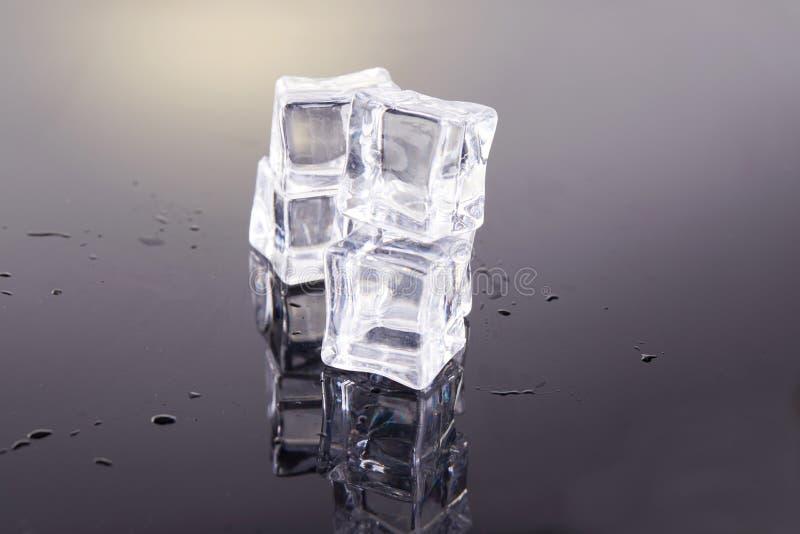 Cubos de hielo apilados por una pirámide en un fondo gris imagenes de archivo