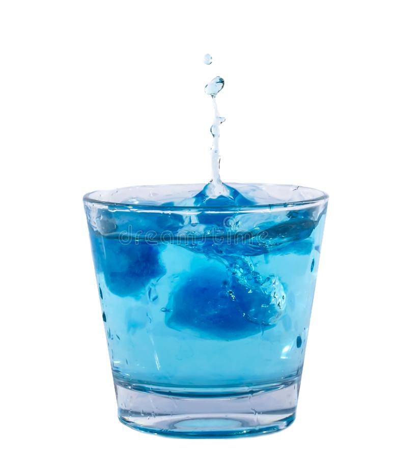 Cubos de hielo azules que salpican en el vaso de agua foto de archivo libre de regalías