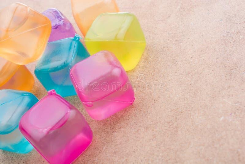 Cubos de hielo coloridos falsos en la madera fotografía de archivo libre de regalías