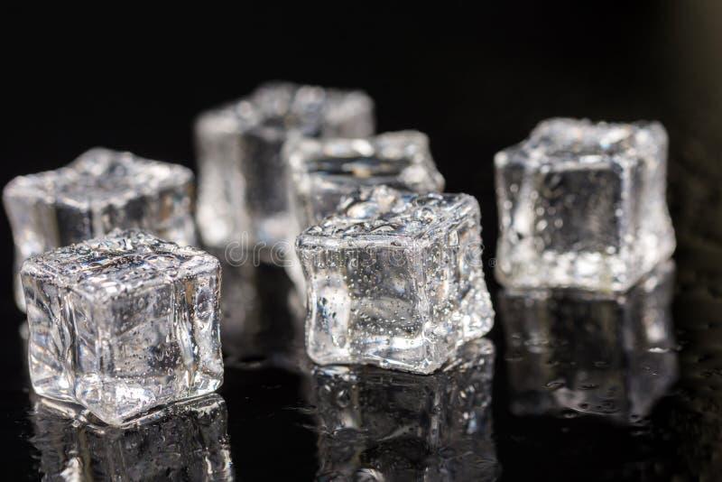 Cubos de hielo con descensos del agua en el fondo negro con reflexiones imagen de archivo