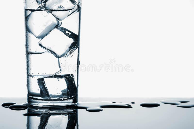 Cubos de hielo en agua potable fresca en vidrio en el fondo blanco fotografía de archivo libre de regalías