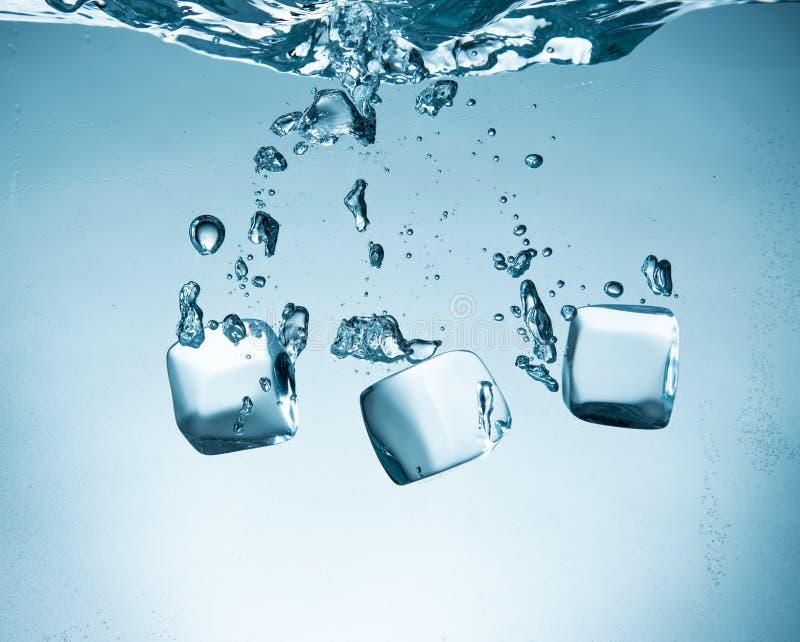 Cubos de hielo que salpican en el agua foto de archivo