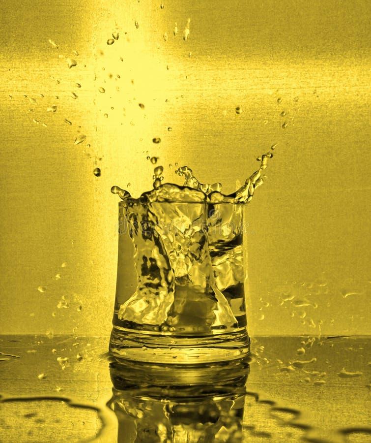 Cubos de hielo que salpican en el vidrio de agua fotos de archivo