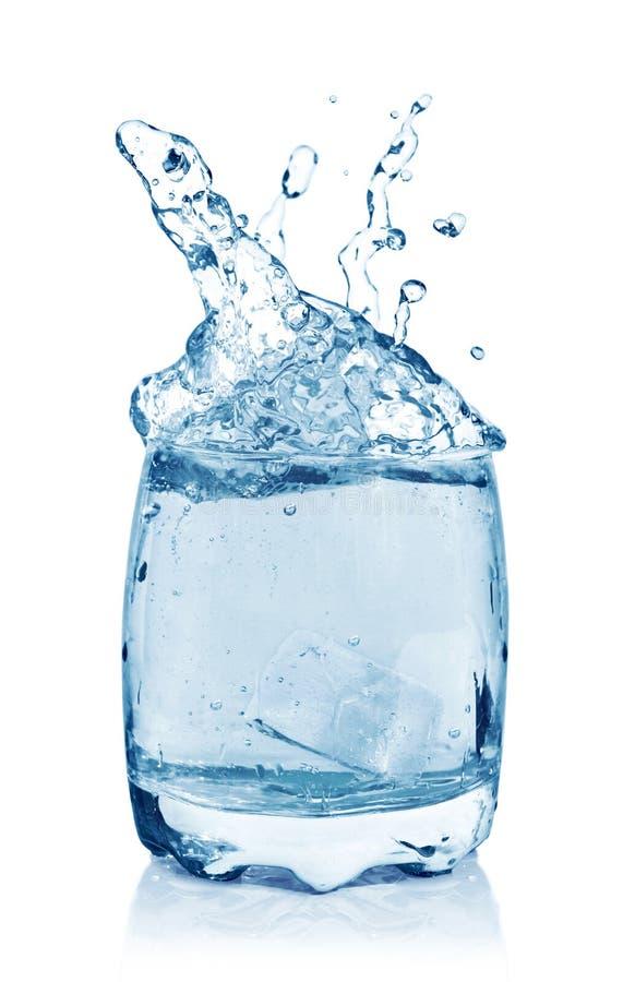Cubos de hielo que salpican en el vidrio de agua imagen de archivo libre de regalías