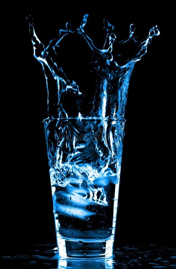 Cubos de hielo que salpican en el vidrio de wate imagen de archivo