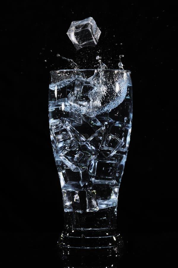 Cubos de hielo que salpican en vidrio imagenes de archivo