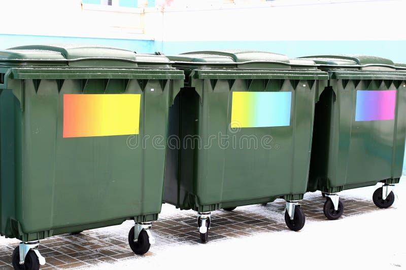 Cubos de la basura verdes sin etiquetas con las etiquetas engomadas coloreadas fotografía de archivo