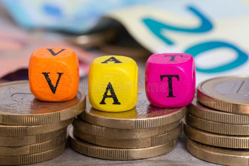 Cubos de la letra del IVA en concepto de las monedas imagenes de archivo