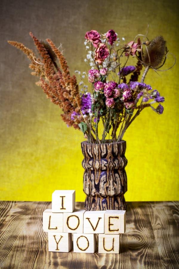 Cubos de madeira com inscrição EU TE AMO e ramalhete de flores secas no fundo novo da placa de madeira e da serapilheira foto de stock