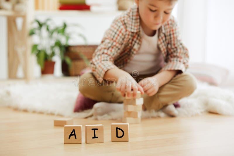 Cubos de madeira com palavra AUXÍLIO nas mãos do rapaz pequeno em casa imagens de stock royalty free
