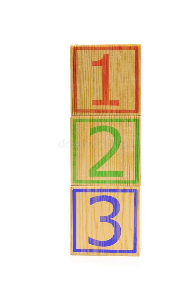 Cubos de madeira marrons empilhados com números um, dois e três imagem de stock royalty free