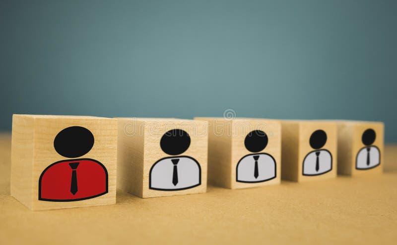 cubos de madera bajo la forma de jefes y subordinados, subordinaci?n de los personales en un fondo azul fotos de archivo