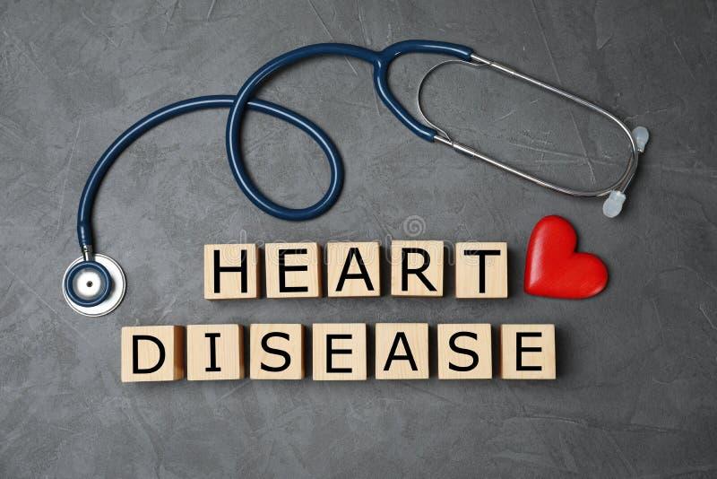 Cubos de madera con enfermedad cardíaca del texto y estetoscopio en fondo gris fotografía de archivo