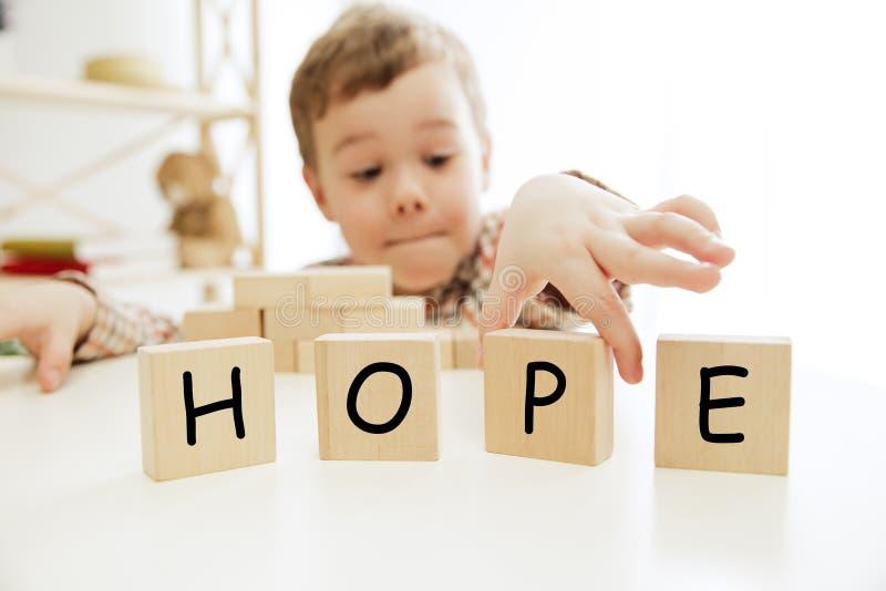 Cubos de madera con la palabra ESPERANZA en manos del niño pequeño foto de archivo libre de regalías