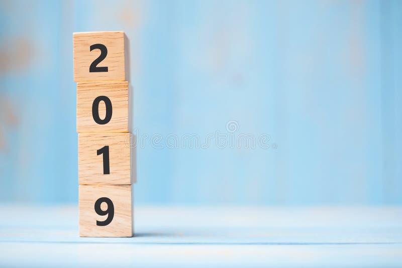 2019 cubos de madera del Año Nuevo en fondo azul de la tabla con el espacio de la copia para el texto Metas de negocio, misión, r fotografía de archivo