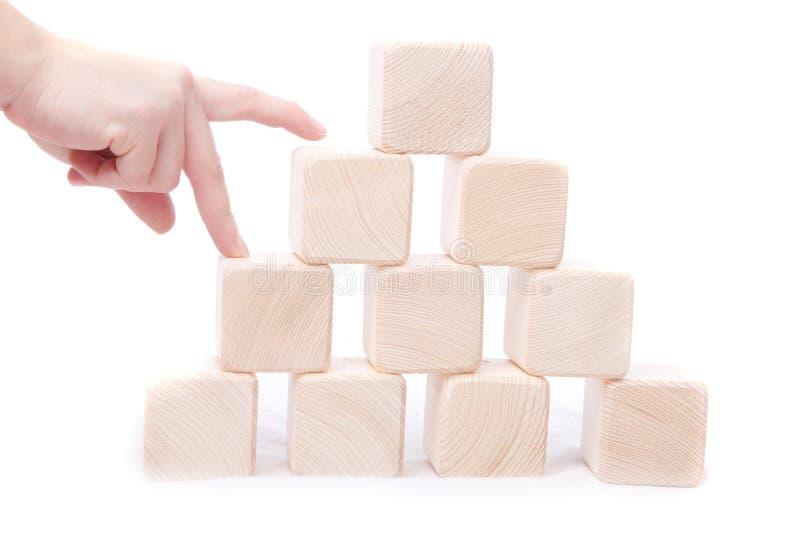 Cubos de madera de la pila La mano establece la torre del bloque aislada imagen de archivo libre de regalías