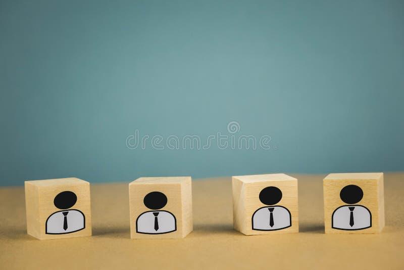 cubos de madera que se colocan en fila, significando a los trabajadores del salario que se colocan en una l?nea, abstracci?n en u imágenes de archivo libres de regalías