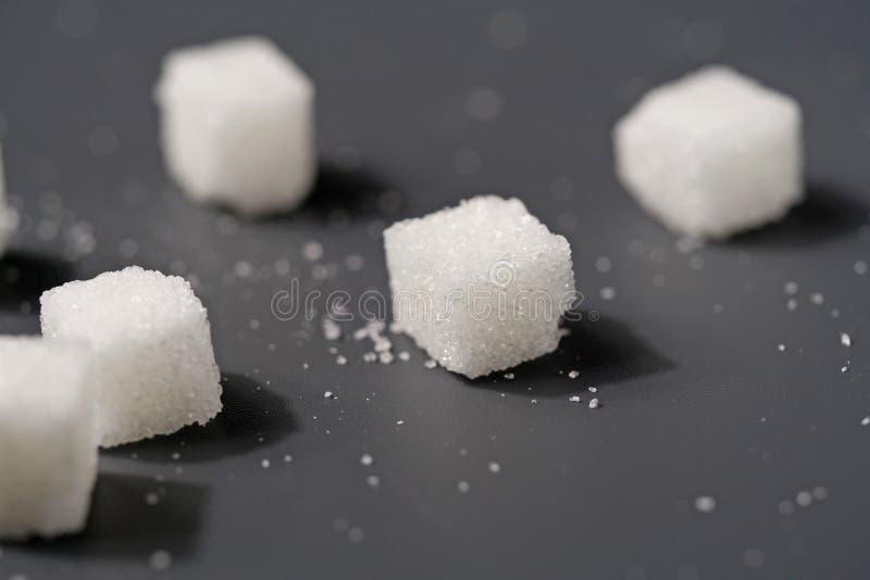 Cubos del azúcar blanco en la tabla negra fotografía de archivo