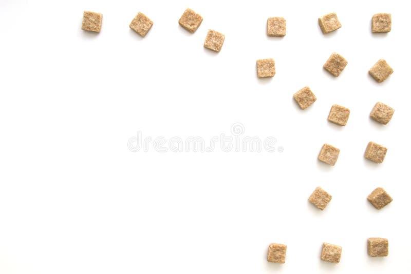 Cubos del azúcar de Brown en el fondo blanco Visión superior Concepto dulce unhealty del apego de la dieta fotos de archivo libres de regalías