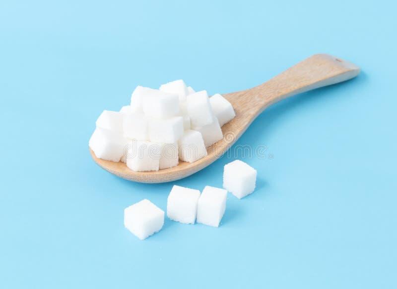 Cubos del azúcar del primer en el fondo azul blanco de la cuchara de madera foto de archivo