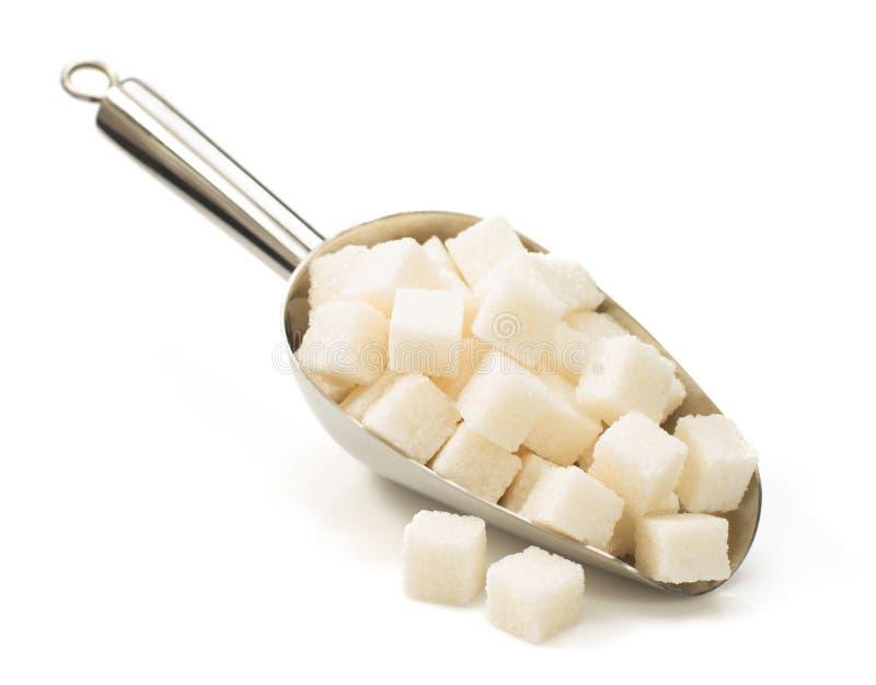 Cubos del azúcar en cucharada en blanco imagen de archivo libre de regalías