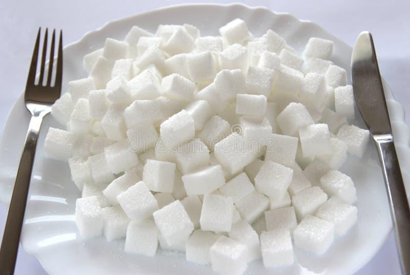 Cubos del azúcar en la placa imágenes de archivo libres de regalías