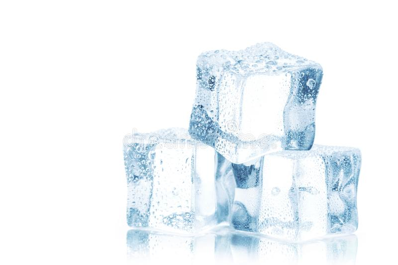 Cubos del hielo claro en una tabla blanca imagen de archivo