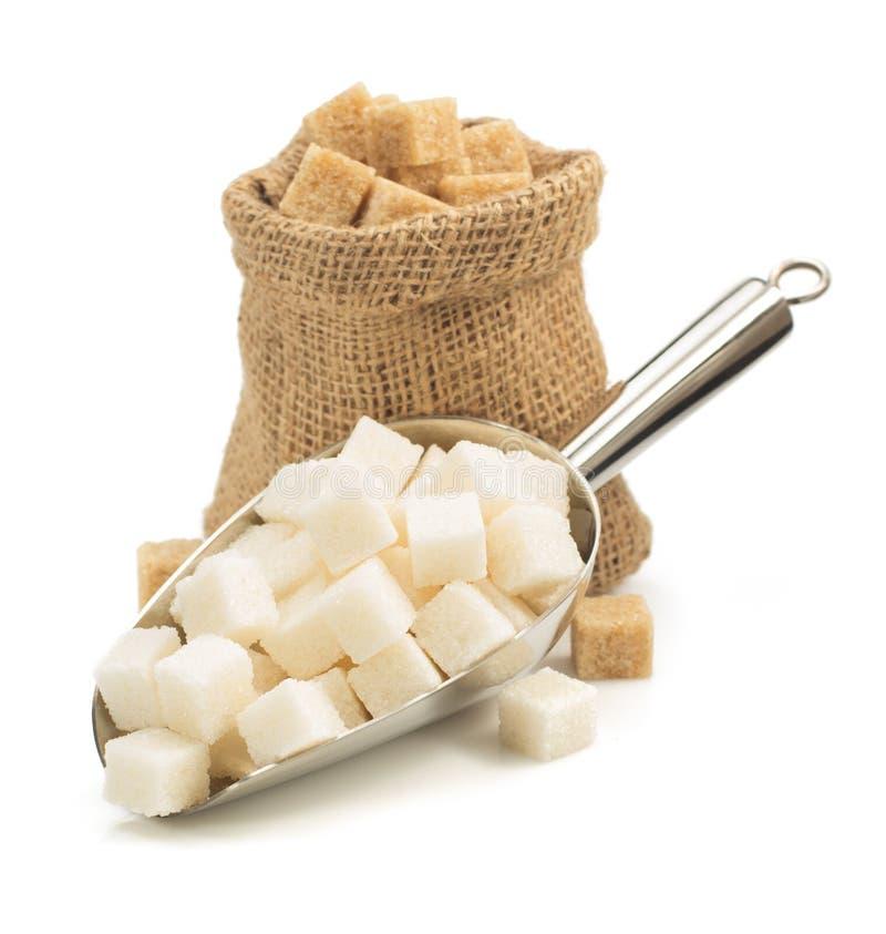 Cubos do açúcar na colher no branco fotos de stock