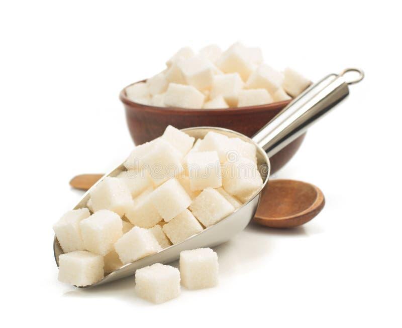 Cubos do açúcar na colher no branco fotografia de stock