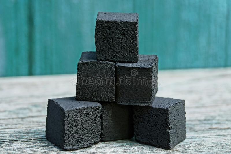cubos do carvão em uma mentira do montão em uma tabela cinzenta imagem de stock royalty free