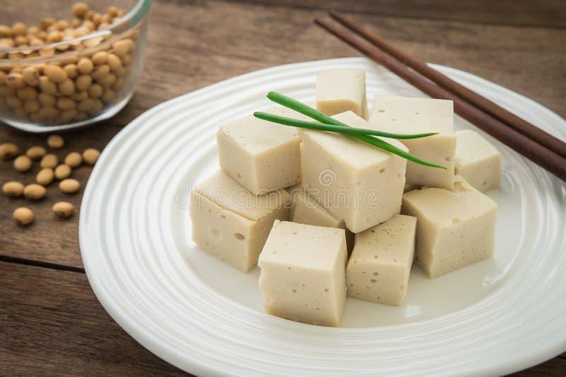 Cubos do Tofu em feijões da placa e da soja na bacia fotos de stock
