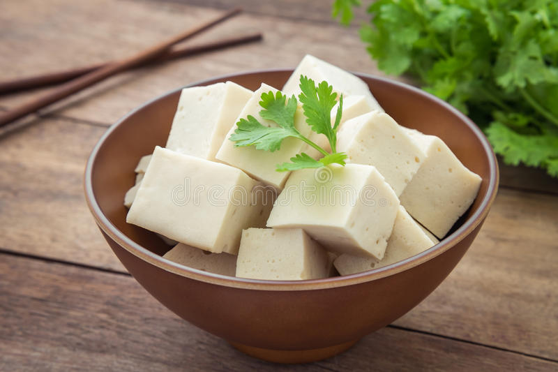 Cubos do Tofu na bacia e na salsa fotos de stock royalty free
