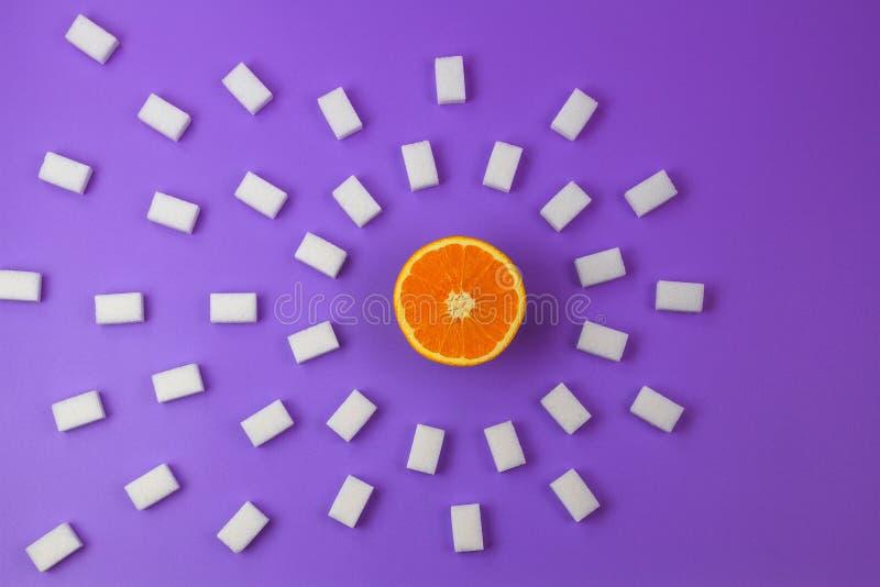 Cubos frescos del azúcar anaranjado y muchos blanco en fondo púrpura fotografía de archivo libre de regalías