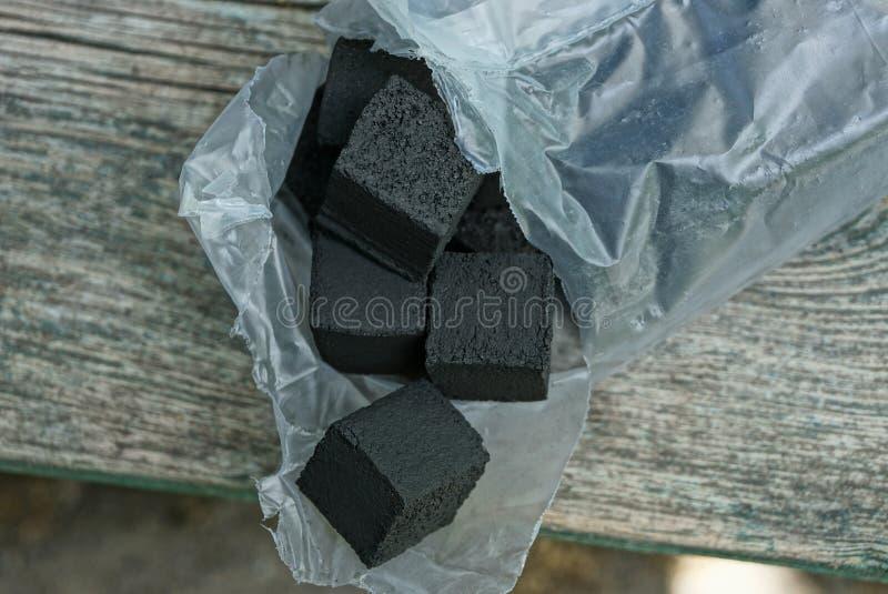Cubos pretos do carvão em um pacote plástico aberto fotos de stock