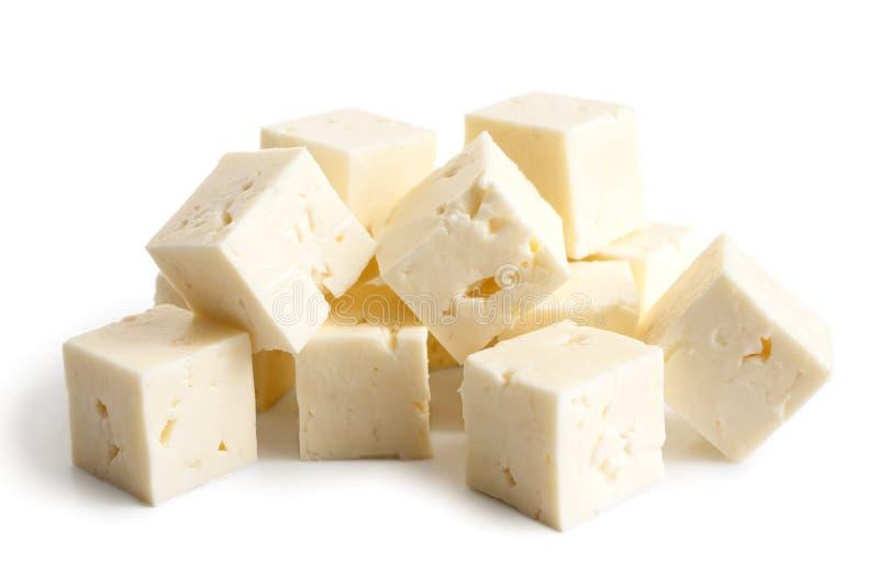 Cubos quadrados do queijo de feta isolados no branco fotos de stock