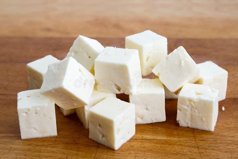 Cubos quadrados do queijo de feta na placa de madeira foto de stock royalty free
