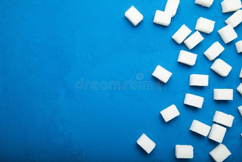 Cubos refinados açúcar em um fundo azul Copie o espa?o foto de stock