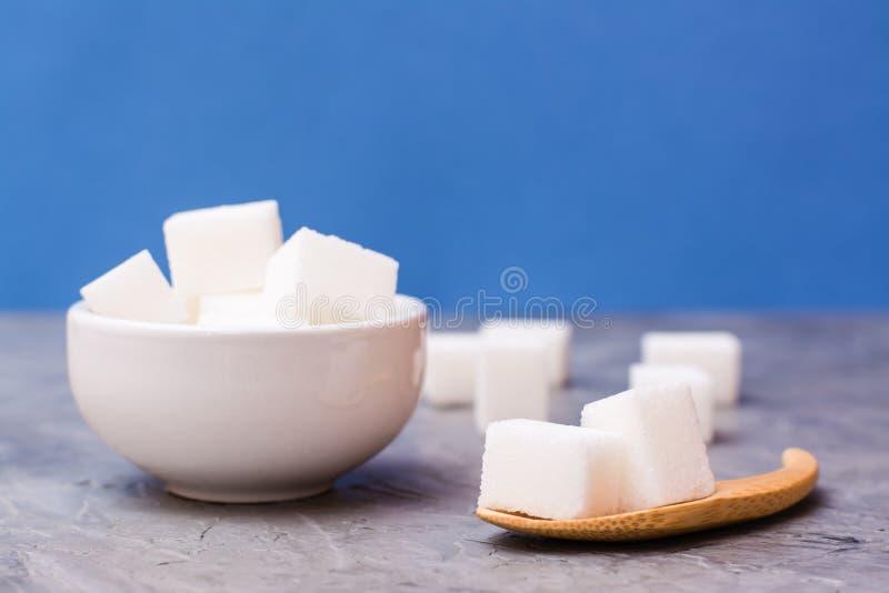 Cubos sin azúcar del azúcar en un cuenco blanco y en una cuchara de madera en una tabla contra foto de archivo libre de regalías