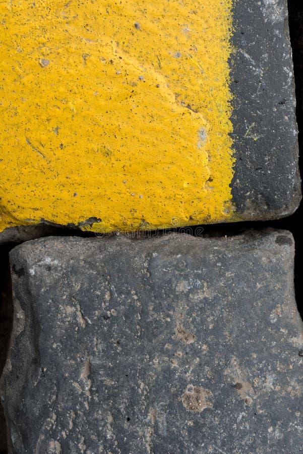 Cubos velhos ou godos amarelos e pretos da estrada do granito como o fundo ou o papel de parede Imagem vertical imagens de stock royalty free