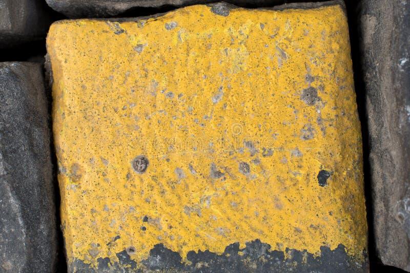 Cubos velhos ou godos amarelos e pretos da estrada do granito como o fundo ou o papel de parede Imagem vertical imagem de stock