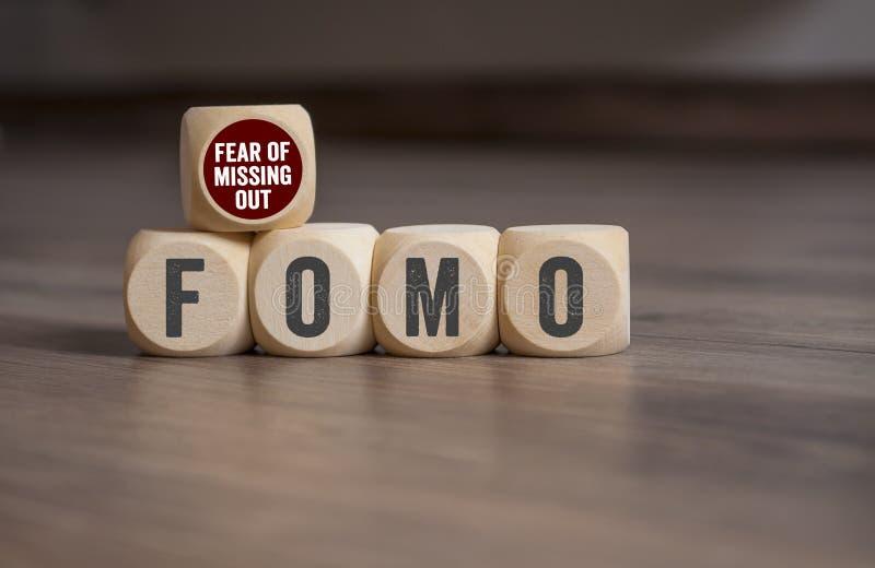 Cubos y dados con el miedo de FOMO de la falta hacia fuera fotografía de archivo libre de regalías