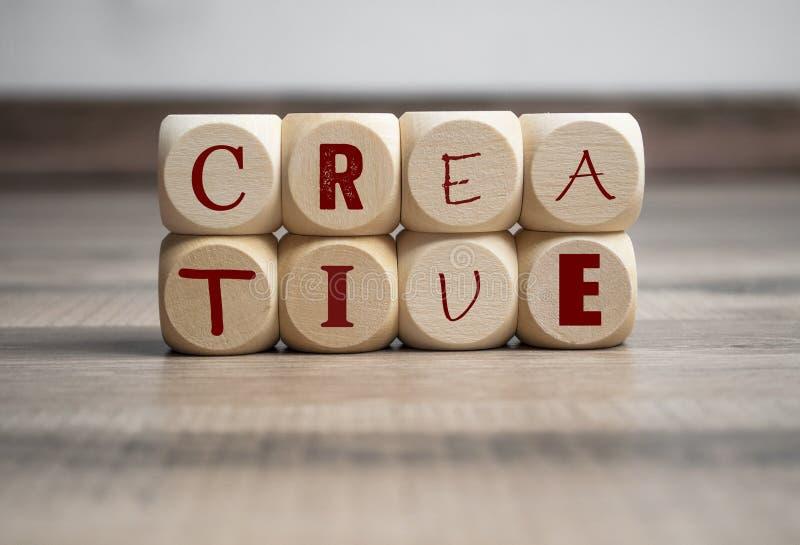Cubos y dados con el término creativo en diversas fuentes imagen de archivo